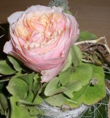 Blumenschmuck für den Tisch mit gefüllten rosa Rosen und Glasperlen